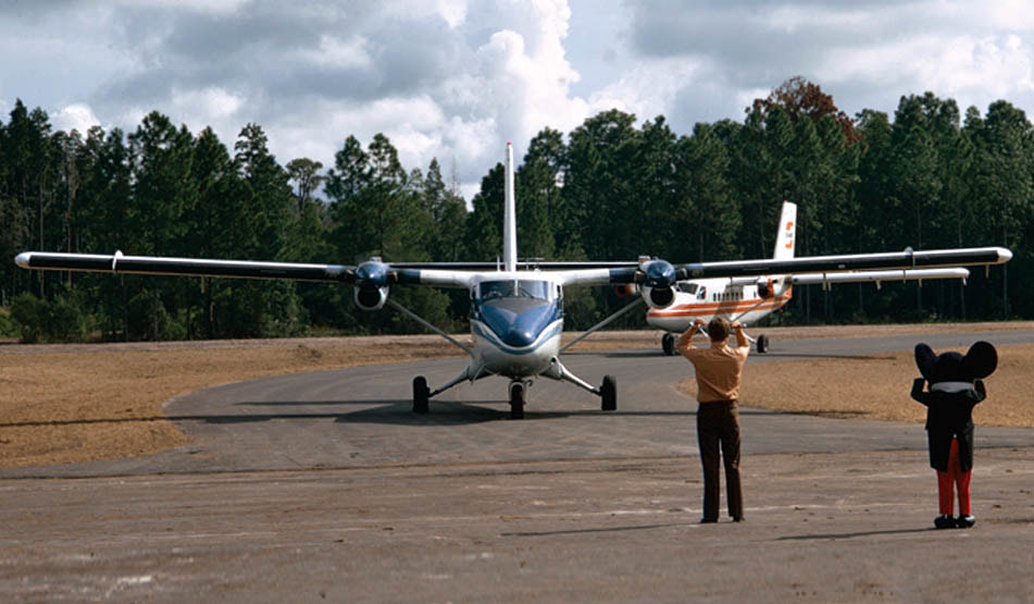 Twin Otters of Executive and Shawnee Airlines are greeted by Mickey Mouse as they arrive at Walt Disney World's Lake Buena Vista STOLport in this 1971 photo.