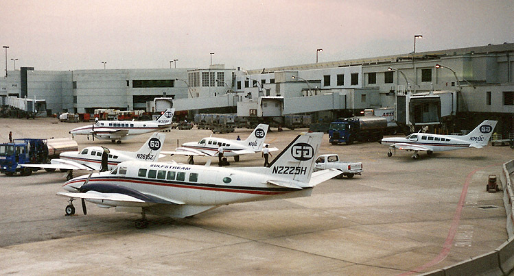 Three Cessna 402s and two Beech 99s sit on the crowded Gulfstream International ramp on a cloudy day in Miami, June 1995.