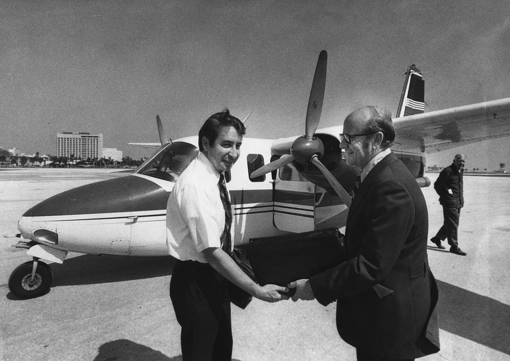 Sun Airlines started regular passenger service to Albert Whitted airport in downtown St. Petersburg in February 1973. Robert Gray (left), pilot and sales director for Sun Airlines welcomes passenger Irwin Miller in front of an Aero Commander used on the flights.